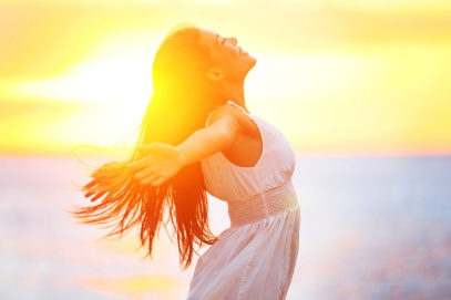 Enjoyment - free happy woman enjoying sunset. Beautiful woman in a white dress embracing the golden sunshine glow of sunset with her arms outspread and face raised to the sky enjoying peace and serenity of nature
